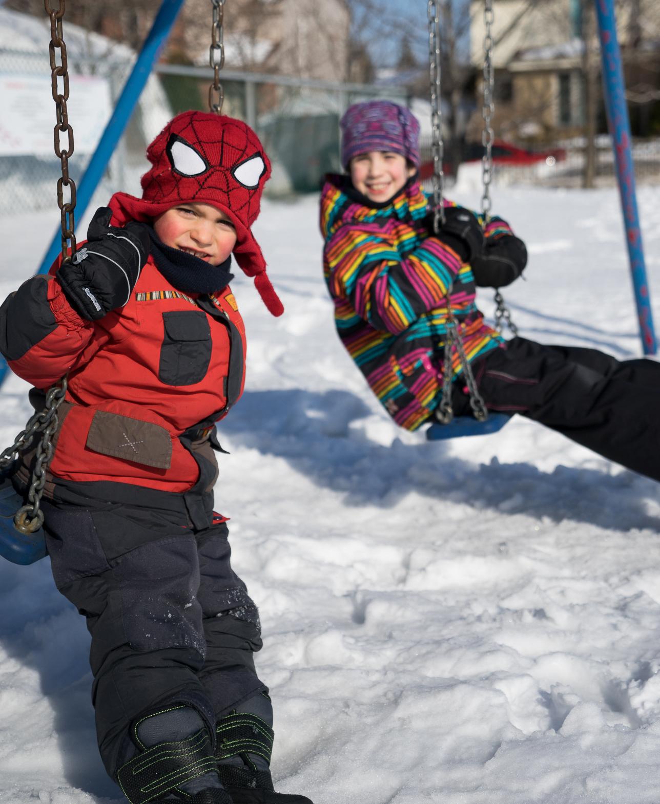 Enfants jouant dehors balancoire hiver