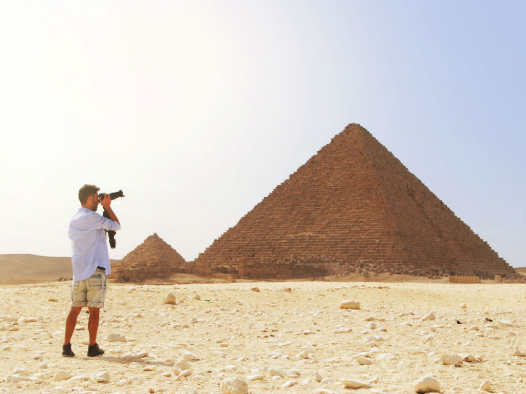 image of man taking photo of pyramid