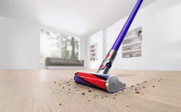 On voit l'aspirateur-balai sans fil V11 Absolute Pro en train de nettoyer un plancher en bois franc dans une salle blanche. Il passe à travers la poussière et les débris sur le plancher en ne laissant rien derrière.