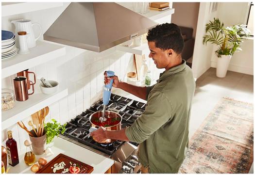 Homme qui cuisine avec un mélangeur à immersion